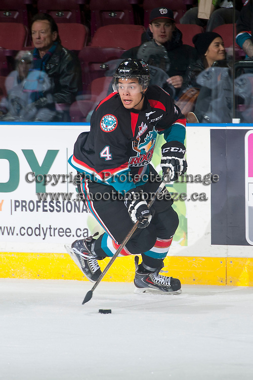 KELOWNA, CANADA - DECEMBER 3: Madison Bowey #4 of Kelowna Rockets skates with the puck against the Saskatoon Blades on December 3, 2014 at Prospera Place in Kelowna, British Columbia, Canada.  (Photo by Marissa Baecker/Shoot the Breeze)  *** Local Caption *** Madison Bowey;