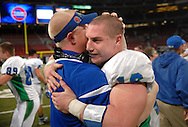 25 Nov. 201 -- ST. LOUIS -- Blue Springs South High School quarterback Connor Harris (16) is congratulated by a member of the Jaguars' coaching staff after they beat CBC High School 40-37 to win the MSHSAA Class 6 state championship Friday, Nov. 25, 2011 at the Edward Jones Dome in St. Louis. Photo © copyright 2011 Sid Hastings.