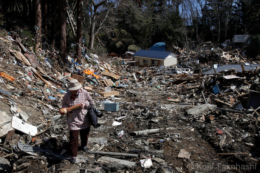 A woman holds her kokeshi-doll she found in the debris in Onagawa, Miyagi, Japan after on March 27, 2011 after massive earthquake and tsunami hit northern Japan and washed her house away. More than 20,000 were killed by the disaster on March 11.<br /> Photo by Kuni Takahashi