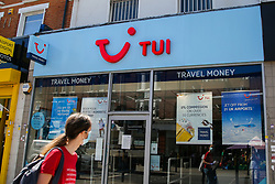 © Licensed to London News Pictures. 30/07/2020. London, UK. A woman wearing a face covering looks at a Tui store on Wood Green High Road in north London. Tour operator Tui announced that 166 high street stores in the UK and the Republic of Ireland will shut due to a downturn in travel caused by the coronavirus pandemic. Photo credit: Dinendra Haria/LNP