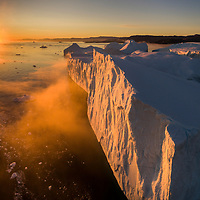 Greenland, Ilulissat, Aerial view of setting midnight sun lighting mist-covered icebergs from Ilulissat Kangerlua Glacier floating in Jakobshavn Icefjord on summer evening.