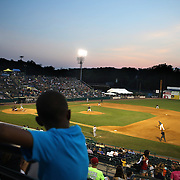 A young spectator watches while hanging on the railings in the stand during the New Britain Rock Cats Vs Binghamton Mets Minor League Baseball game at New Britain Stadium, New Britain, Connecticut, USA. 2nd July 2014. Photo Tim Clayton
