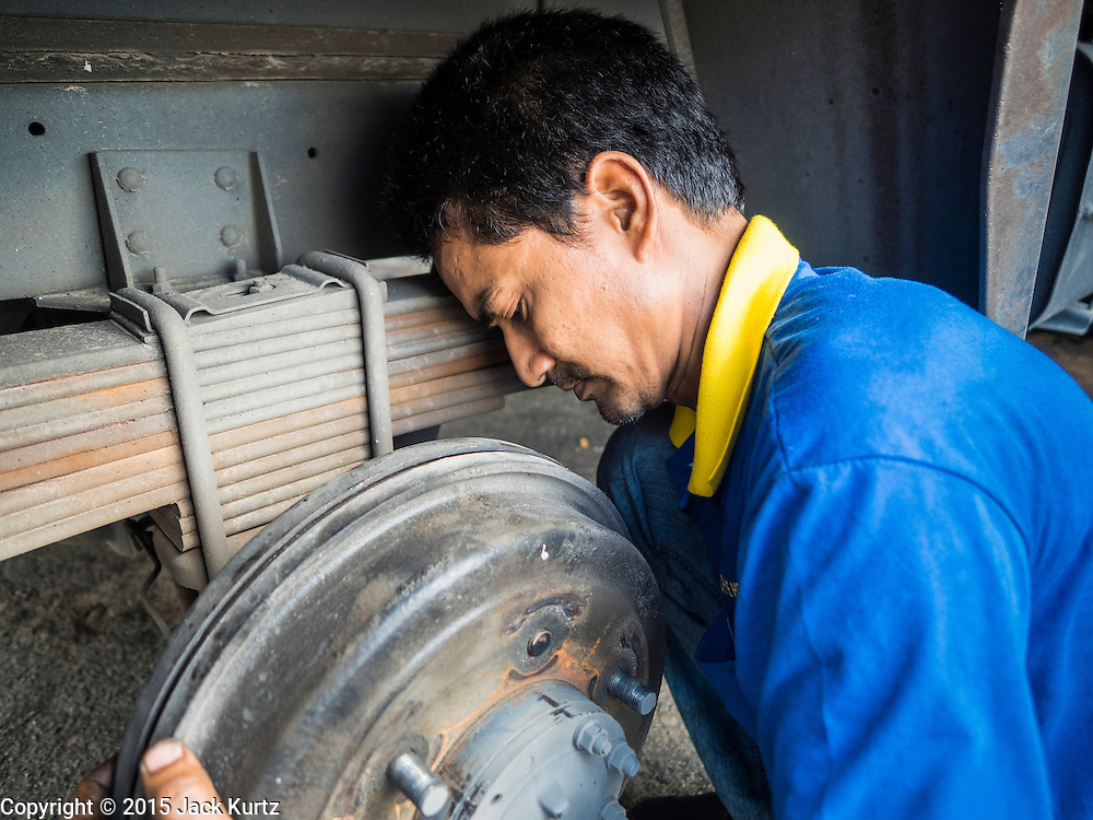 03 JUNE 2015 - KULAI, JOHORE, MALAYSIA: A Rohingya refugee who works as a truck mechanic, works on the brakes of a delivery truck in Kulai, Malaysia. The UN says the Rohingya, a Muslim minority in western Myanmar, are the most persecuted ethnic minority in the world. The government of Myanmar insists the Rohingya are illegal immigrants from Bangladesh and has refused to grant them citizenship. Most of the Rohingya in Myanmar have been confined to Internal Displaced Persons camp in Rakhine state, bordering Bangladesh. Thousands of Rohingya have fled Myanmar and settled in Malaysia. Most fled on small fishing trawlers. There are about 1,500 Rohingya in the town of Kulai, in the Malaysian state of Johore. Only about 500 of them have been granted official refugee status by the UN High Commissioner for Refugees. The rest live under the radar, relying on gifts from their community and taking menial jobs to make ends meet. They face harassment from Malaysian police who, the Rohingya say, extort bribes from them.    PHOTO BY JACK KURTZ