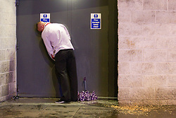 © licensed to London News Pictures. Manchester, UK 01/01/2012. New Years Day revellers in Manchester. A man urinates in a fire exit doorway, beside a discarded umbrella and a puddle of vomit. Please see special instructions for usage rates. Photo credit should read Joel Goodman/LNP