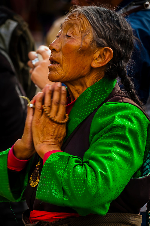 Tibetan woman praying and prostrating herself in Barkhor Square, outside the Jokhang Temple (the most sacred temple in Tibet), Lhasa, Tibet, China.