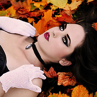 A pretty girl with pale skin, long black hair and heavy make-up lying in colorful autumn leaves.