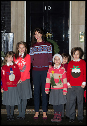 Samantha Cameron in a Christmas jumper and purple heels to greet young fundraisers from St Nicholas school outside 10 Downing Street this morning..Prime Minister David Cameron's wife congratulated the schoolchildren for raising more than £500 by taking part in Save the Children's Christmas Jumper Day, where people wear a festive sweater and donate £1, Friday December 14, 2012 Photo By Andrew Parsons / i-Images
