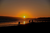 Woman and Dog  on the beach  at sunset in  Silhouette