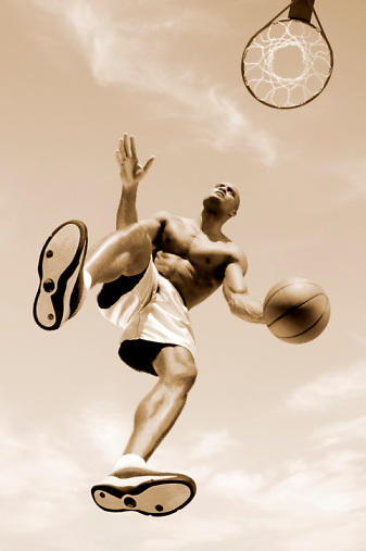 Man jumping in air with basketball, low angle view