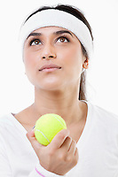 Young ambitious female tennis player looking up over white background