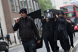 © licensed to London News Pictures. London, UK 22/05/2012. Occupy London protesters marching to Shell's AGM with a mock coffin prepared for Shell and a flag with Shell's logo drawn as a skull in central London today (22/05/12). Photo credit: Tolga Akmen/LNP