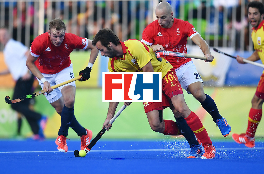 Spain's David Alegre (C) is tackled by during the Great Britain's Nick Catlin mens's field hockey Britain vs Spain match of the Rio 2016 Olympics Games at the Olympic Hockey Centre in Rio de Janeiro on August, 12 2016. / AFP / MANAN VATSYAYANA        (Photo credit should read MANAN VATSYAYANA/AFP/Getty Images)