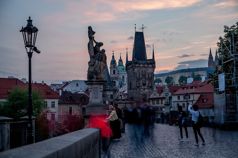 Crowds visiting during thr evening Charles Bridge which is a historic bridge that crosses the Vltava river in Prague and one of the main attractions in the city. Its construction started in 1357 under the auspices of King Charles IV and finished in the beginning of the 15th century.