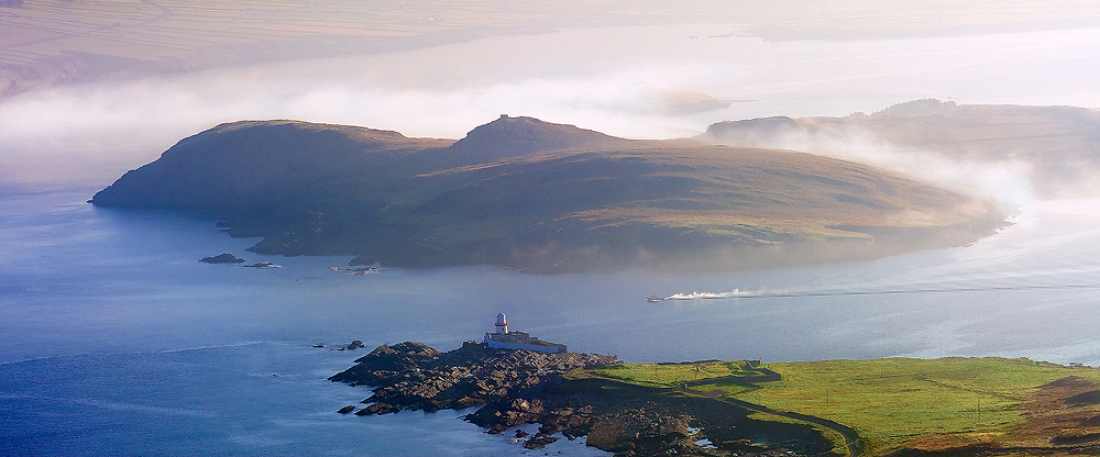 Valentia Island Lighthouse and Begenish Island during misty Sunrise with fisher boat / vl106