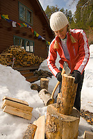 A young woman splits firewood in Jackson Hole, Wyoming.