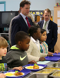 © Licenced to London News Pictures. 04/12/2013. London. UK.  <br /> Deputy Prime Minister Nick Clegg and Schools Minister David Laws are pictured in the school canteen with children on their visit to the Walnut Tree Walk Primary School in London, December 4th 2013. The Deputy Prime Minister announced in September that one of his key priorities for the Autumn Statement was to provide free school meals to every infant school pupil.<br /> Photo Credit: Susannah Ireland