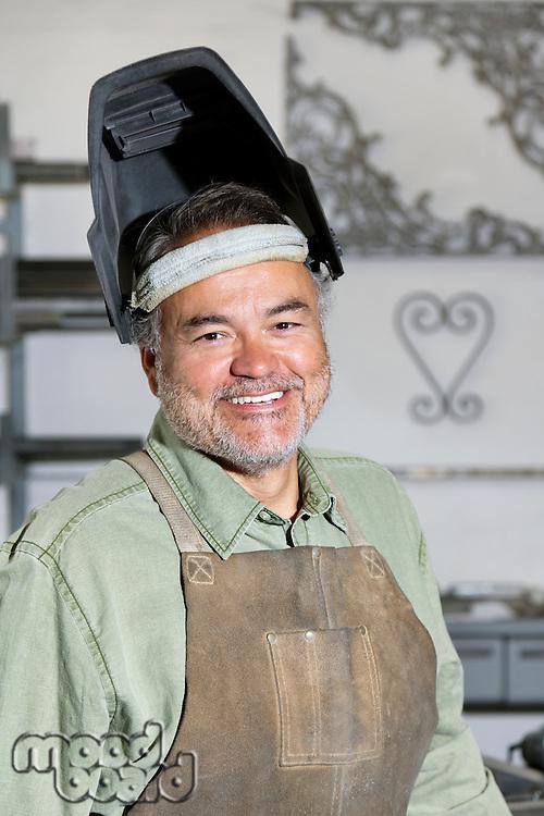 Portrait of a happy mature man wearing welding mask in workshop