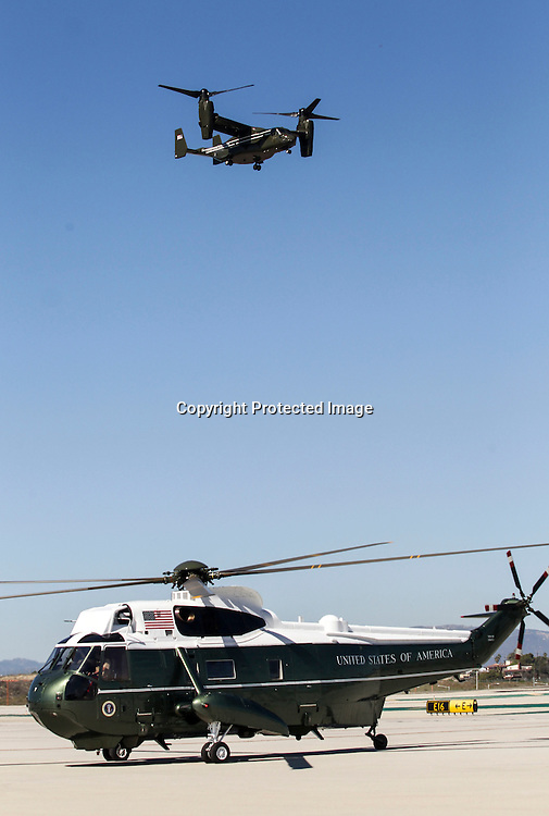 "An ""Osprey"" aircraft flies over the Marine One before President Barack Obama's arrival at Los Angeles International Airport in Los Angeles on Saturday, Oct. 10, 2015. (AP Photo/Ringo H.W. Chiu)"
