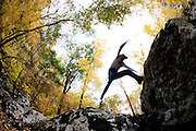 Person jumping across boulders in the woods in the Fall.