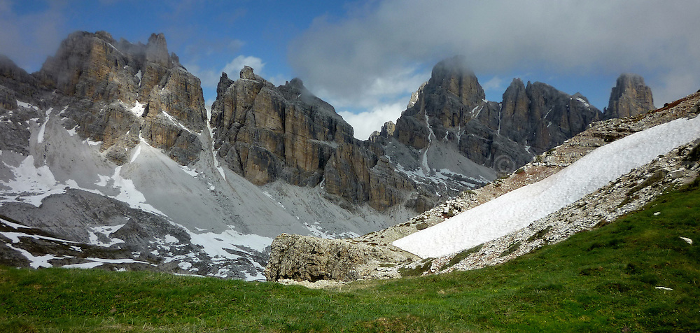 Clouds rolling over the Italian Dolomites just as the snow melts and the grass reappears.