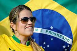 A female fan of Brazil with a flag