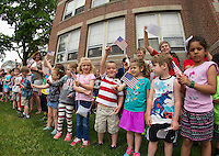 Holy Trinity Catholic School students wave their flags during a Memorial Day service on the front lawn Friday morning.  (Karen Bobotas/for the Laconia Daily Sun)