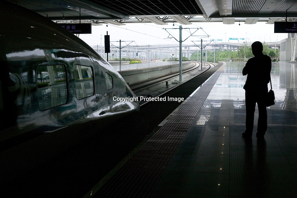 Beijing, September 11 , 2011 : a man stands next to the TGV to Beijing. the passenger-dedicated trunk line opened in June 2011, reducing the 1,318 km journey between Beijing and Shanghai to less than 5 hours. Trains reach top speeds of 300 km/h (186 mph) for the entire trip.