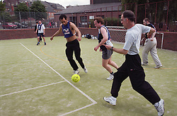 Group of men playing game of football on artificial pitch,