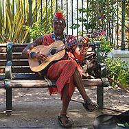 A South African Street Musician plays the guitar in a park.