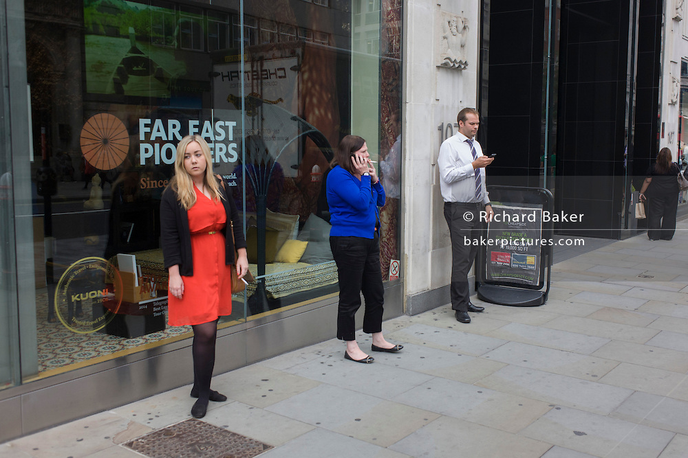 Three city workers in blue, red and white, stand outside an office building in the City of London.