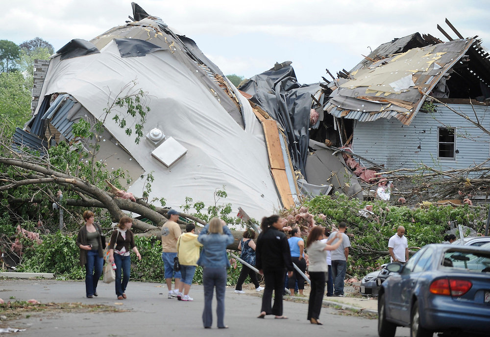 People photograph and look at storm damage a day after a tornado in Springfield, Mass., Thursday, June 2, 2011. Massachusetts public health officials say about 200 people have sought treatment for a variety of storm-related injuries, and a Springfield regional trauma center says at least three have injuries so severe they may need long-term rehabilitation. (AP Photo/Jessica Hill)
