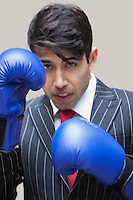Portrait of an Indian businessman wearing blue boxing gloves against gray background