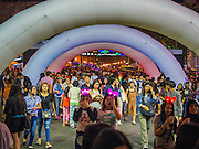 31 DECEMBER 2014 - BANGKOK, THAILAND: People walk into the New Year's party in Rathaprasong. Hundreds of thousands of people pack into the Ratchaprasong Intersection in Bangkok for the city's annual New Year's Eve countdown. Many Thais go the Erawan Shrine and Wat Pathum Wanaram near the intersection to pray and make merit before going to their New Year's parties.    PHOTO BY JACK KURTZ