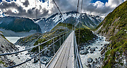 Glacier-clad Mount Sefton rises above the foaming Hooker River at the second swing bridge over Hooker Valley Track, in Aoraki / Mount Cook National Park, Canterbury region, South Island, New Zealand. In 1990, UNESCO honored Te Wahipounamu - South West New Zealand as a World Heritage Area.