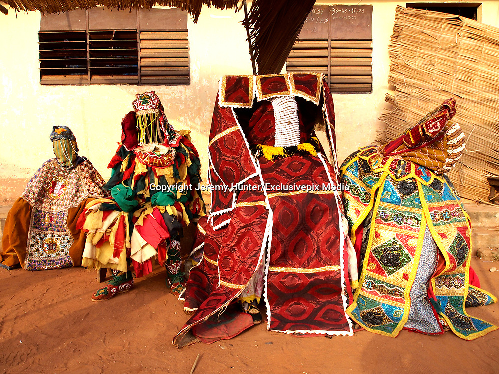 """EXCLUSIVE PICTURE FEATURE<br /> The Living Ghosts of Benin<br /> <br /> *Villagers believe if they are touched by an Egungun, they will die<br /> <br /> *Having any contact whatsoever with an Egungun can prove deadly for both the Egungun and the other person, so each Egungun is accompanied by a 'minder', also a member of the Egungun society, who carries a long and substantial stick to drive individuals away...<br /> <br /> <br /> <br /> BENIN is a small country sandwiched between Nigeria to the East and Ghana and Togo to the West. Formerly a French colony known as Dahomey, little is known about the country prior to around the 15th century when it was occupied first by the Portuguese, then the British, Dutch and lastly French who ousted King Behanzin and took control in 1894. <br /> <br /> The Egungun are one of Benin's Secret Societies who appear as masked men representing the spirits of the Living Dead. They are Living Ghosts, a conduit to the ancestors. Their role in village society is to settle local disputes, and their knowledge is often consulted in times of trouble within their village. The Egungun speak in a high-pitched and altogether un-human and unsettling falsetto tone, similar to the voices used in a Punch-and-Judy show, and in a language that is not understood by other villagers; they are always accompanied by drummers. Some say they derive their name from the Yoruba (Northern Nigerian) word for """"bones"""" or """"skeleton,"""" but in Yoruba, Egungun also means """"masquerade.""""  Egungun arrive in villages, pass judgements and give advice. Their word is final as their advice is a direct word of the Gods.<br /> <br /> Each Egungun appears as a robed figure - giving the impression that the deceased is making a temporary reappearance on Earth. This impression is enhanced by the voluminous costumes of the Egungun; the cloth and design they use expresses the power of the ancestor. In one village I came across an Egungun with the stature and form of a child. I enquired as """