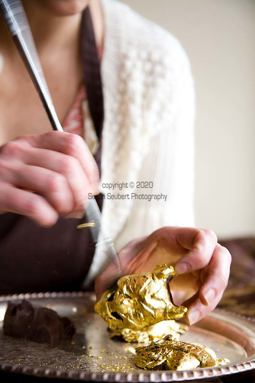 """Sarah Hart, owner of Alma Chocolates, a botique chocolate shop in Portland, Oregon, creates """"Day of the Dead"""" sweets among other beautiful confections. Here she is putting the finishing touches on her gold leafed chocolates."""