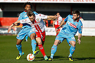 Luke Freeman of Stevenage (centre) is fouled by Junior Brown of Tranmere Rovers (left) while Steve Jennings of Tranmere Rovers (right) looks on during the Sky Bet League 1 match at the Lamex Stadium, Stevenage<br /> Picture by David Horn/Focus Images Ltd +44 7545 970036<br /> 08/03/2014