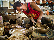 02 AUGUST 2018 - PAK KRET, NONTHABURI, THAILAND: Workers make Mon style pottery in a pottery factory on Ko Kret. Ko Kret (also spelled Koh Kret) is a small island in the Chao Phraya River in Nonthaburi province north of Bangkok. It is about 2 km long and 1 km wide. It has seven main villages, the largest and most populous being Ban Mon. Ko Kret was created in 1722 when a canal was dug in the Chao Phraya River to bypass a bend. Most of the people on the island are ethnically Mon, from the hills of western Thailand and eastern Myanmar (Burma). The island is popular as a weekend daytrip from Bangkok. The island is famous for the Mon style pottery made on the island.      PHOTO BY JACK KURTZ
