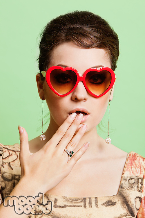 Portrait of shocked young woman wearing heart shaped sunglasses against green background
