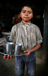"""RUKUM DISTRICT, NEPAL, APRIL 24, 2004:  A child works in a tea stall in a small village in Rukum District April 24, 2004. Nepal is one of the poorest countries and most children are forced to be a part of the labor work force.  Ill-equipped security forces in politically unstable Nepal are unable to control  Maoist rebels, who continue to abduct thousands of villagers for forcible indoctrination and military training.  The Maoists mainly target students, teachers and youths. The victims are usually released after a few days of indoctrination, unless they actively resist the """"training attempts,"""" in which case the rebels torture or sometimes kill them. Maoist insurgents have capture most of the Western part of Nepal in their attempt to make it a Communist State. Analysts and diplomats estimate there about 15,000-20,000 hard-core Maoist fighters, including many women, backed by 50,000 """"militia"""".  In their remote strongholds, they collect taxes and have set up civil administrations, and people's courts. They also raise money by taxing villagers and foreign trekkers.  They are tough in Nepal's rugged terrain, full of thick forests and deep ravines and the 150,000 government soldiers are not enough to combat this growing movement that models itself after the Shining Path of Peru. (Ami Vitale/Getty Images)"""