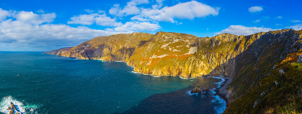 View overlooking the Slieve League Cliffs from Bunglass viewpoint. This one is from my holiday to Donegal back at the end of October 2014. This time the weather was much brighter than when I was last here the year before. With being a similar time of year the orange ferns on the rugged slopes of the cliffs were on show again, with the bright sun giving a much warmer feel to the image. Off in the far distance you can see Rathlin O'Birne island and its lighthouse, as well as the Napoleonic signal tower at Malin Beg.<br /> <br /> Image composed of 5 photos at 85mm in portrait orientation offering stunning levels of detail. You can zoom in and take a closer look to see what this could look like on your wall here http://adambrooks.photoshelter.com/#!/p/I0000FGppKTfmV7Y<br /> <br /> Available in sizes ranging from 8&quot;x20&quot; - 20&quot;x50&quot; (20cmx51cm - 51cmx127cm).