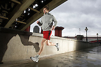 Young man jogging besides the Thames in London on stormy day