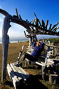 Image of a woman sitting on a driftwood bench overlooking the Pacific Ocean in Yachats, Oregon, Pacific Northwest, model and property released