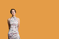 Happy mid adult woman standing over colored background