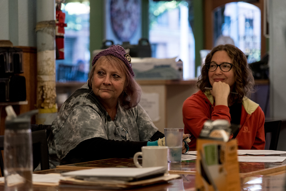 "Cherie (left), an Aquarius and cafe regular, listens at a training session for new volunteers. She came to Portland from Florida ""after my husband divorced me, put me in an RV and said 'have a nice life.'"""