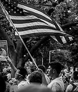 A man holds the American flag before a May Day march in Washington, DC, USA 01 May 2017. Labor Day or May Day is observed all over the world on the first day of the May to celebrate the economic and social achievements of workers and fight for laborers rights.