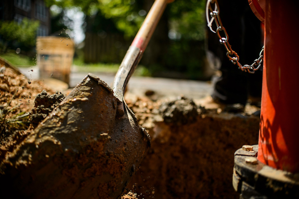 Photo by Matt Roth<br /> <br /> Baltimore City Department of Public Works site supervisor Nathaniel Copeland, shovels wet concrete into the cavity during a fire hydrant replacement call at the intersection of Tyndale Ave., and Canfield Ave. in Baltimore, Maryland on Wednesday, May 29, 2013.