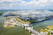 Nederland, Zuid-Holland, Rotterdam, 10-06-2015; Nieuwe Botlekbrug.<br /> De brug over de Oude Maas is een hefbrug, een van de twee brugdelen in geheven toestand. De heftorens van de oude brug gaan verscholen achter de nieuwe brug. Olietanks van Odfjell Terminals en Essoraffinaderij in de achtergrond. Ingang Botlektunnel links naast de nieuwe brug.<br /> New Botlek bridge. The bridge over the Oude Maas is a vertical-lift bridge or lift bridge, one of the two bridge sections raised. <br /> luchtfoto (toeslag op standard tarieven);<br /> aerial photo (additional fee required);<br /> copyright foto/photo Siebe Swart