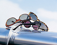 Catalog photography of three sunglasses photographed on the silver wing on an airplane for Charles Keath.