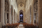 Nave of the Collegiate Church of Saint-Gervais-Saint-Protais, built 12th to 16th centuries in Gothic and Renaissance styles, in Gisors, Eure, Haute-Normandie, France. The church was consecrated in 1119 by Calixtus II but the nave was rebuilt from 1160 after a fire. The church is 70m long and the nave is 24m high with a rib-vaulted ceiling. Here we look East towards the altar, chevet and rose window. The church was listed as a historic monument in 1840. Picture by Manuel Cohen